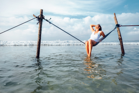 Woman sits in hammock swing over ocean surf line - island summer holiday