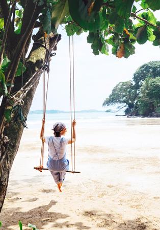 유행 옷을 입은 여자는 넓은 모래 바다 해변에서 나무 그네에 앉는다. 스톡 콘텐츠