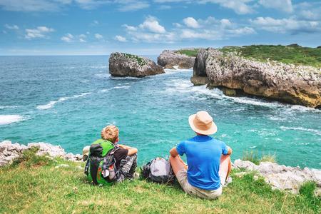 I viaggiatori con zaino e sacco a pelo di padre e figlio riposano sul lato roccioso del mare e si godono con una splendida vista Archivio Fotografico - 94929483