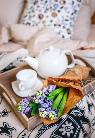 Bouquet hyacinth flowers and teapot with fresh tea are on bed