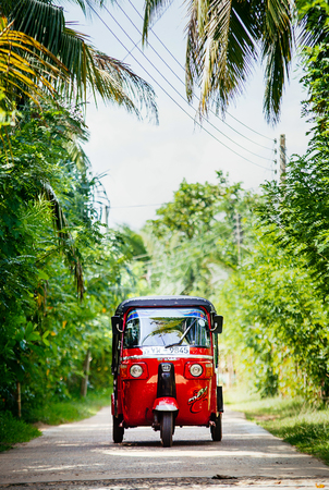 Weligama, Sri Lanka – December 27, 2017: Red tuk-tuk under the palm trees on the country road in Weligama, Sri Lanka Editorial
