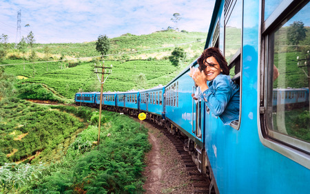 Happy smiling woman looks out from window traveling by train on most picturesque train road in Sri Lanka Archivio Fotografico