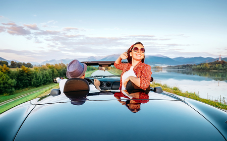 Couple in love ride in cabriolet on the picturesque mountain road Stockfoto