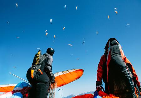 Zwei Gleitschirme mit voller Flugausrüstung schauen sich an, wie ein weiterer Gleitschirm in den Himmel fliegt Standard-Bild