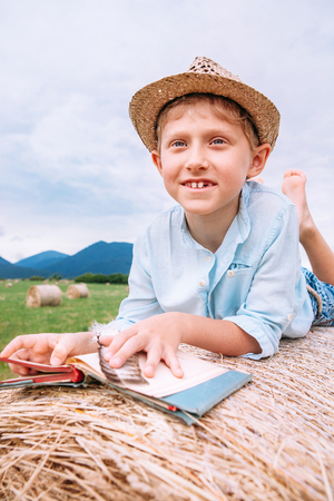 Boy with book lies on the hay roll
