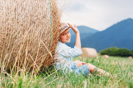 Boy sit on the field under the hay roll - careless summet in country side Stock Photo