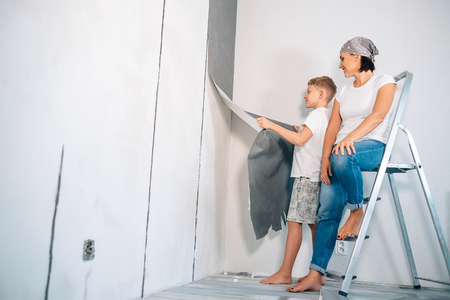 Mother and son take off wallpapers from wall and prepare room for renovation