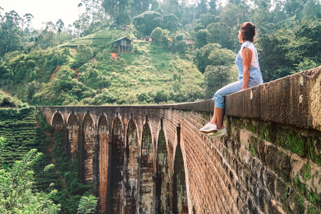 Woman sits on the Demodara nine arches bridge the most visited sight of Ella town in Sri Lanka Stok Fotoğraf - 95585060