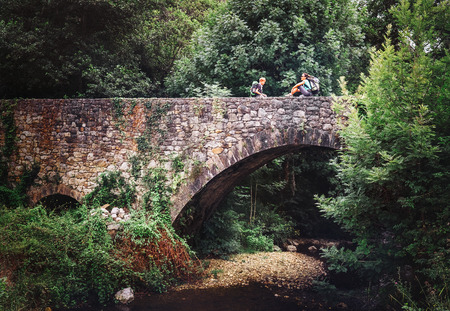 Mother and son sit on old viaduct bridge over the forest river 写真素材