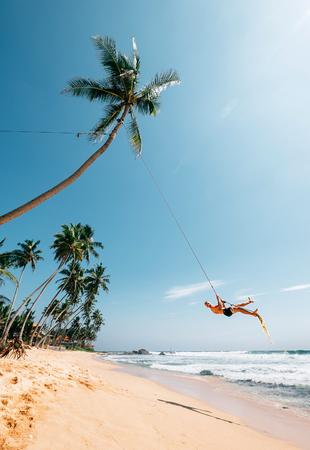 Happy man dangles on tropical palm tree swing Stock Photo