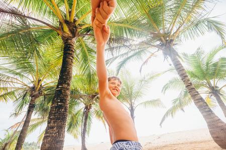 Il ragazzo prende per mano suo padre e lo tira sulla soleggiata spiaggia dell'oceano