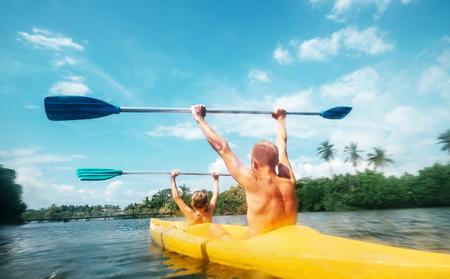Vater und Sohn segeln im Kanu in der Lagune am sonnigen Tag