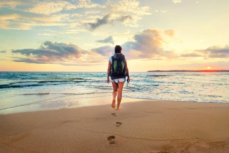 Woman with backpack walk on the ocean sand beach at sunset time Stock Photo
