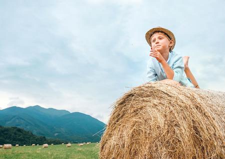 Careless boy lies on haystack roll on the mountain field