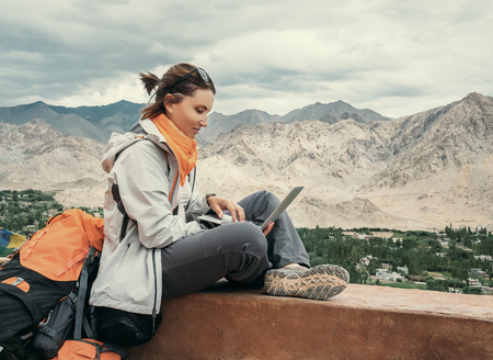 Backpacker with laptop sits on the top view point under mountain settelment Reklamní fotografie - 97052295