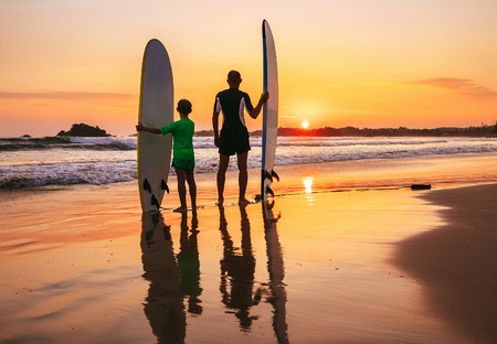 Father and son surfers stay on the sunset beach Foto de archivo