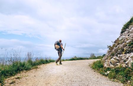 Backpacker traveler walks on road