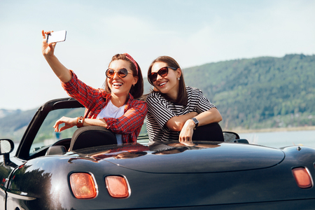 Two female freinds take a selfie photo in cabriolrt car during their summer voyage Archivio Fotografico