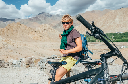 Young man bike traveler rest on high mountain road in Himalaya Stock Photo