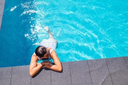 Woman swim in swimming pool at sunny day