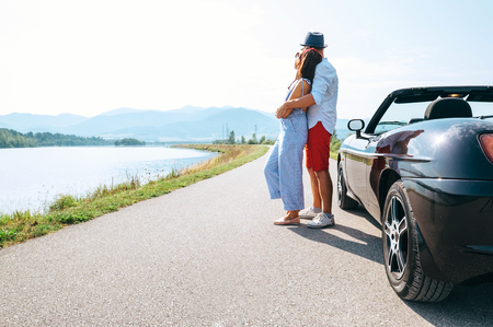 Couple in love stands near the cabriolet car on the picturesque mountain road Stock Photo