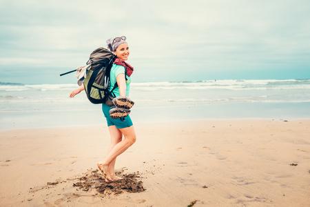 Happy girl backpacker traveler runs barefoot on the sand ocean beach