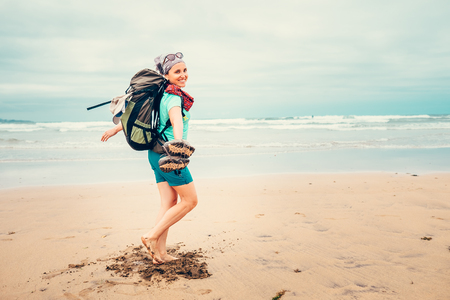Happy girl backpacker traveler runs barefoot on the sand ocean beach