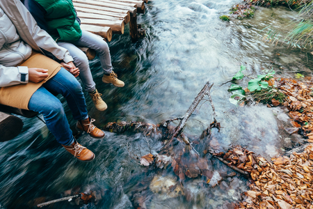 Mother and son sit on the wooden bridge over the mountain stream