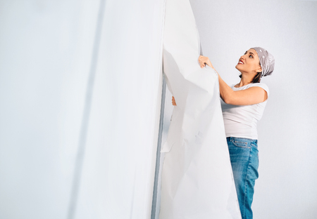 Woman prepare room for renovation, take off wallpapers from wall Stock Photo