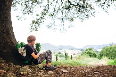 Little backpacker traveler rest under tree on country road Stock Photo