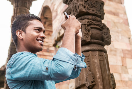 Indian young man take a mobil photo Stock Photo