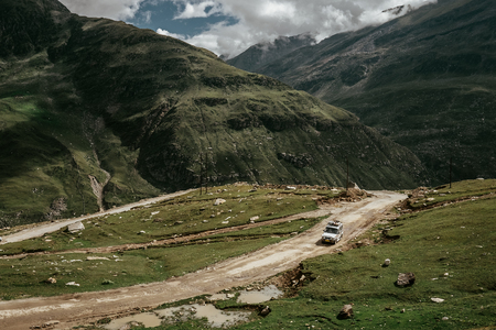 Off road expedition vehicle on the mountain road among Himalaya hills