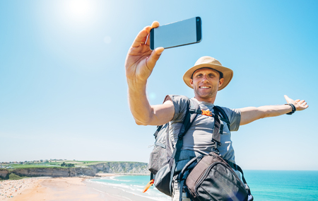Backpacker traveler take a self photo with smartphone on beautiful ocean view Foto de archivo - 99375802