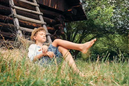 Little lazy boy sleeps under old hayloft in garden Stockfoto