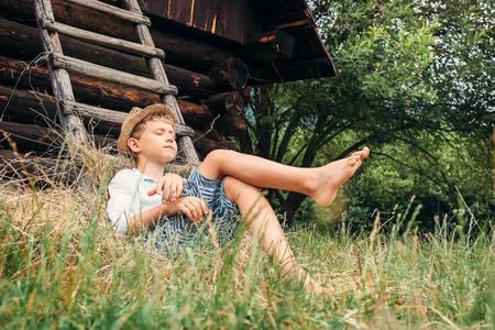 Little lazy boy sleeps under old hayloft in garden Banque d'images