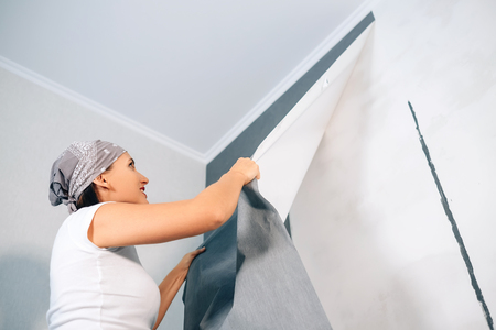 Woman take of wallpapers from wall