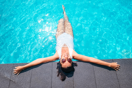 Smiling woman in big sunglasess relax in swiming pool on luxury resort