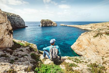 Backpacker traveler relax on the rocky coast of blue sea lagoon