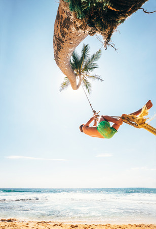Little boy dangles on tropical swing on the palm tree