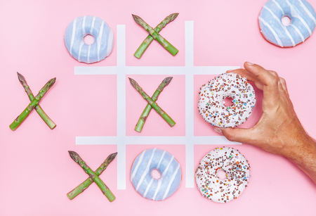 Playing in tik tak toe game with donuts and asparagus. Health nutrition concept image Banco de Imagens