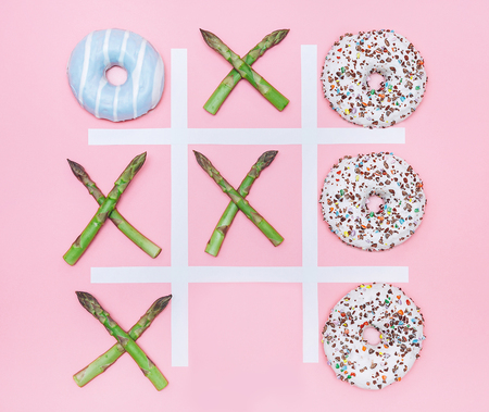 Tik tak toe game with donuts and asparagus. Health nutrition concept image