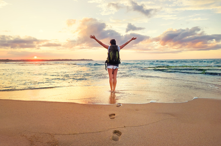 Woman backpacker stay on ocean surf line at sunset time Archivio Fotografico - 99969234