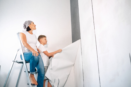 Mother and son take off wallpapers together and prepare room for renovation Stock Photo