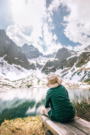 Boy traveler rests near beautiful mountain lake. Spring summer hiking, active leisure concept image