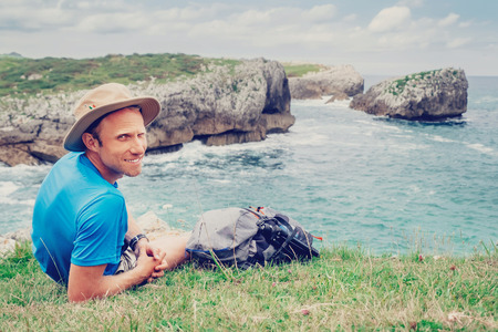 Man backpacker traveler rests on the rocky sea side, looks in camera and smile