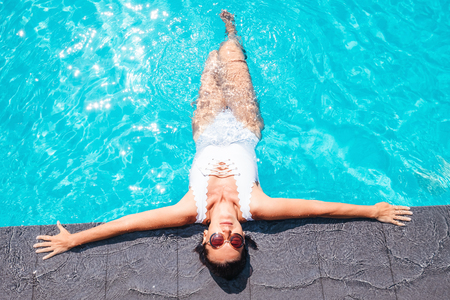 Woman in white swimsuit relax in swiming pool on luxury resort Stock Photo