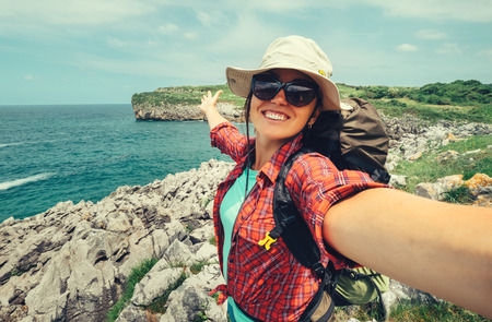 Happy woman backpacker traveler take a selfie photo on amazing ocean coast Stock Photo