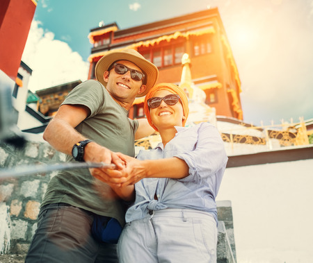 Tourist couple take a self photo on tibetian sight background