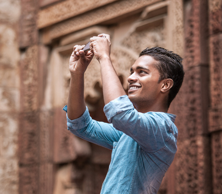 Indian young man take a mobil photo of local architect sight Stock Photo