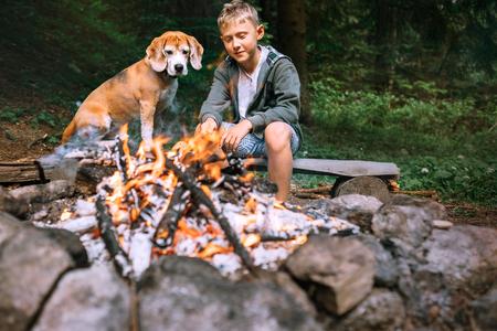 Boy with beagle dog roast a food on campfire